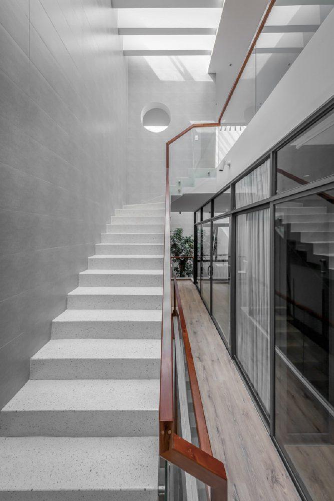 Cầu thang ốp đá và màu tường trung tính mang lại cảm giác sạch sẽ và thoáng mát